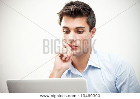 Young thoughtful business man working at the notebook