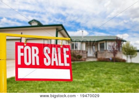 Real estate sign in front of a house for sale focus on the sign
