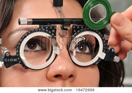 Beautiful young female patient having a medical examination at optician - a series of eye exam related pictures.