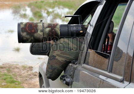 Bird photographer taking photos with camouflaged telephoto lens.