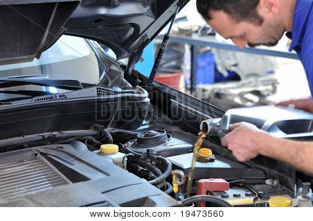 Car mechanic changing oil - model and oil motion blurred.