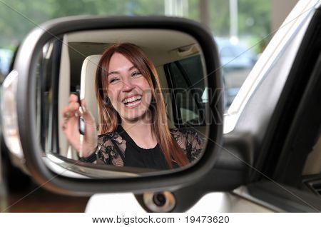 Reflection of a red head woman buying a new car - a series of BUYING A NEW CAR images.