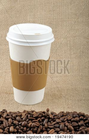 Paper coffee cup with safety cardboard collar on jute background with coffee beans and copy space.