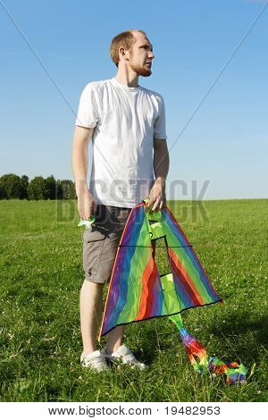 Young Man In White Shirt Standing On Summer Meadow And Holding Multicolored Kite
