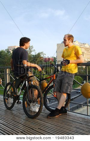 Two Young Men In Sport Clothes Standing On Bridge Near Bicycles And Talking