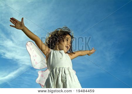 young girl with fairy wings flying against blue sky with cirrus clouds