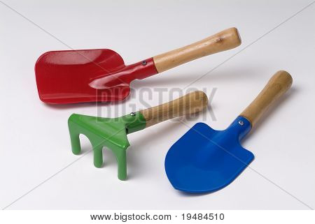 red shovel, green rake and blue spade,  kids garden tools.