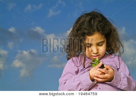little girl holding a plant against cloudy blue sky