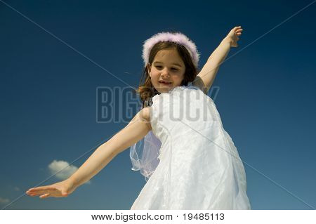 young girl with spreads arms against blue sky