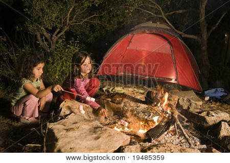 two girls having fun at a bonfire eating marshmallow