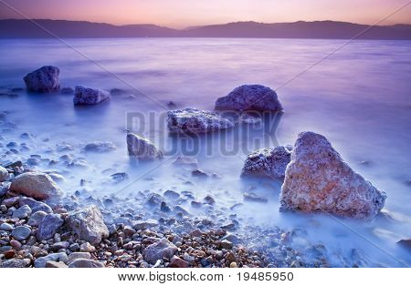 sunrise over the dead sea with waves in motion blur