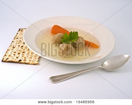 traditional passover matzo ball soup with spone and matza.
