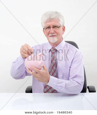 senior man holding a hammer breaking a piggy bank over white