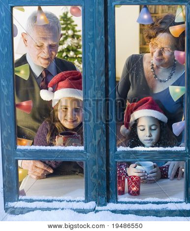 Grandparents and granddaughter at the window on Christmas eve.