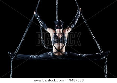 Young woman gymnast in cat suit. On black background.