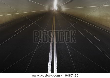 photo of empty concrete tunnel with lines converging in the light