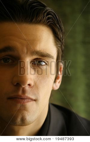 close up of a young man's face against green background