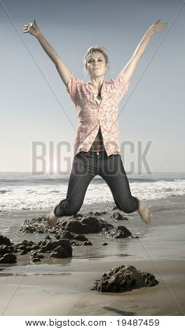 Hip young model jumping in midair on beach