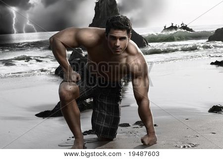 Dark stylized portrait of a young muscular shirtless man on the beach with storm and crashing waves in background
