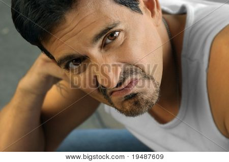 Tough looking man in white tank top expressing disgust