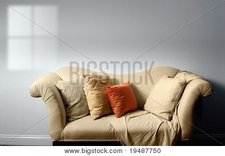 Elegant sofa with pillows against bare white wall