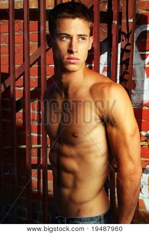 Sexy shirtless male model in street alley with graffiti