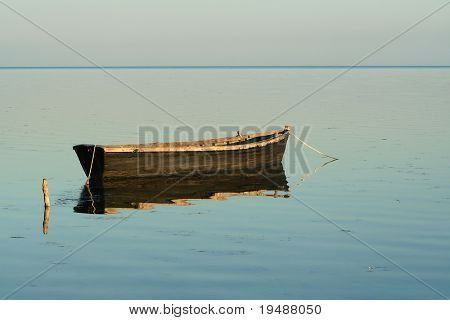 Lonely boat in the quiet sea sundawn. Water iron also reflection