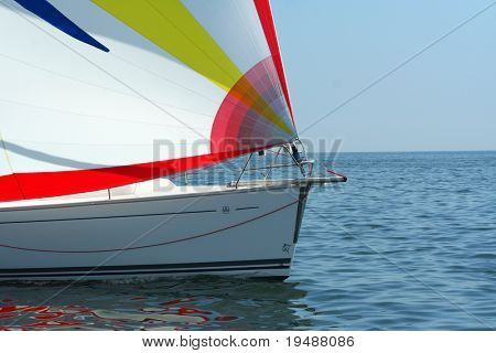 Magnificent yacht with a colour sail. Beautiful reflection in water. This Pleasant time.