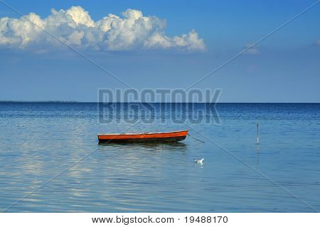 On this sea landscape all lonely one boat, one seagull and one cloud a Beautiful idyllic landscape
