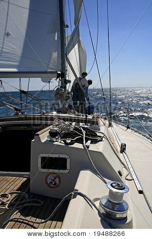 Two men work with sails.  Aboard a beautiful yacht there is a rigging, cords and blocks.