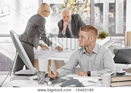 Designer team at work in office, young architect sitting at desk with drawing pad, older colleagues working on architectural plan.?