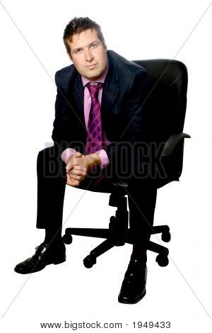 Confident Businessman Sitting On Leather Office Chair