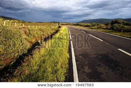 Open road leading through wide field embedded in mystical ambiance on  Isle of Skye, Scotland
