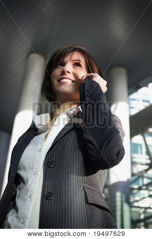 Young confident female professional talking on mobile phone in front of office building