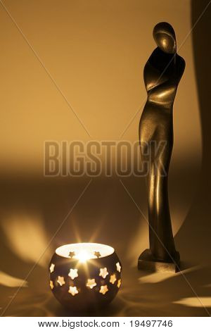 Cast Madonna with folded hands looking down at candle