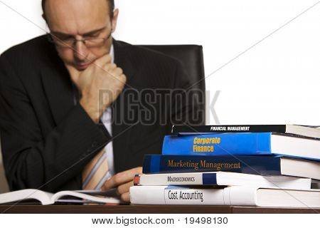 Businessman in suit sitting at desk in office in front of a stack of business books studying information, white background