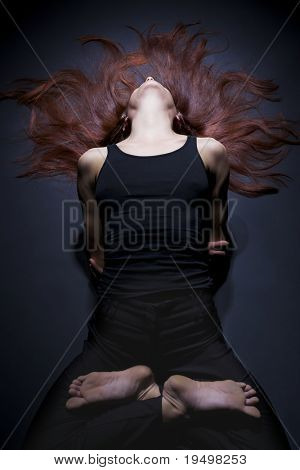 Young lady practicing yoga in lotus fish posture (Matsyasana) in black clothes with red hair spread out on dark background, high-key image.