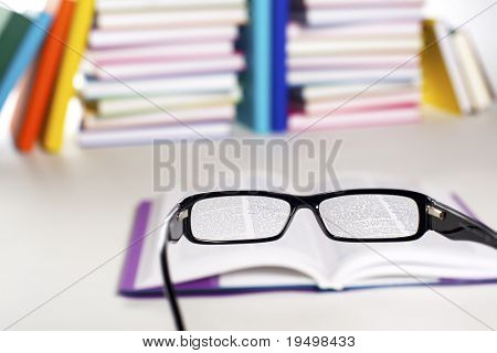 Clear view through specs facing open book in front of stack in rainbow colors paper wrapped books on white background,  PHOTOGRAPH, NOT 3D RENDER.