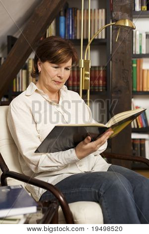 Pretty senior woman sitting in chair at home in front of bookshelves reading a book.