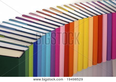 Close-up of curve aligned in rainbow colors paper wrapped books with blank spine facing front, view from top-left, PHOTOGRAPH, NOT 3D RENDER.