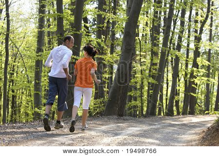 Happy couple jogging together on gravel path in beech forest, view from behind.
