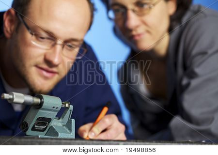 Close-up of young male engineer in blue overall recording precision measurement data of metal toothed wheel in screw micrometer and assistant in background watching him, isolated on blue background.