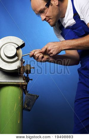 Close-up of young male technician in blue overall working on grinding bench in workshop, isolated on blue background.