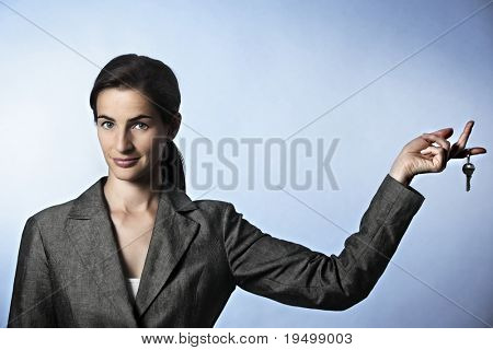 Concept: Unlock opportunities, Portrait of business woman with key hanging on finger.