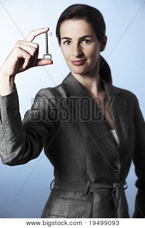 Concept: The Key to Success, Portrait of business woman holding key between fingers, focus on key.