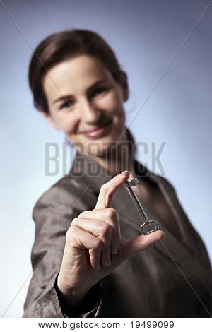 Close-up of smiling business woman holding key between fingers, focus on key.