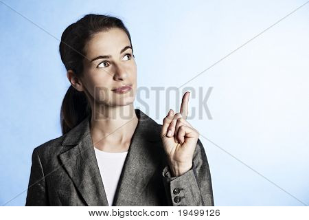 Portrait of young smiling businesswoman pointing upwards on light blue background.