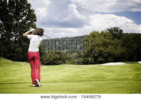 Female golf player teeing-off golf ball at beautiful golf course with forest.