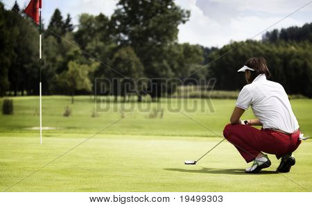 Female golf player with putter squatting to analyze the green at golf course.