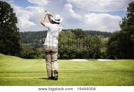 Male golf player teeing-off golf ball at beautiful golf course with forest.
